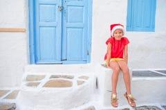 户外圣诞老人帽子的小女孩在老街道圣诞节假期在米科诺斯岛 在典型的希腊语街道的孩子  免版税库存照片