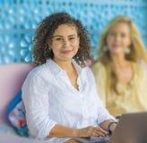 户外在与便携式计算机,一个女孩白种人的凉快的咖啡馆的两个女性朋友,另一个妇女非洲混合了 库存图片