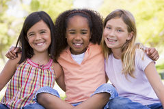 户外坐三个年轻人的朋友女孩 免版税库存图片