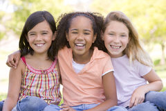 户外坐三个年轻人的朋友女孩 免版税库存照片