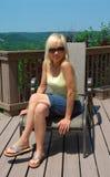 户外坐妇女的金发碧眼的女人 免版税库存照片