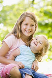 户外坐微笑的二的姐妹 免版税库存照片