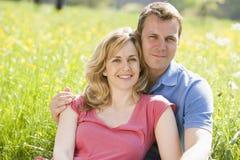 户外坐微笑的夫妇 免版税库存照片
