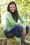 户外坐微笑的妇女森林的日志 免版税库存图片