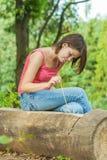 户外坐森林的女孩日志 免版税库存照片