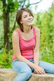 户外坐森林的女孩日志 免版税图库摄影