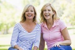 户外坐的微笑二名妇女 免版税库存图片