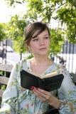 户外女孩与圣经 免版税库存照片