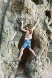 户外女孩孩子爬与蝴蝶面孔绘画的树 免版税库存图片