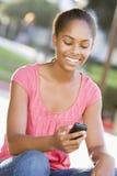 户外女孩移动电话给坐的少年使用打电话 免版税库存照片