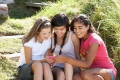 户外女孩给少年使用打电话 免版税库存图片