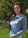 户外女性学院/大学生,固定的单元电话手机 免版税库存照片