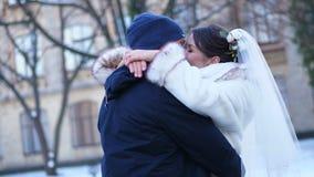 户外婚姻冬天的新娘新郎 在婚纱的新婚佳偶夫妇 新婚佳偶亲吻,拥抱 恋人浪漫亲吻  他们是愉快的 影视素材