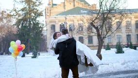户外婚姻冬天的新娘新郎 在婚纱的新婚佳偶夫妇 新郎拿着他的胳膊的新娘,转动 他们是愉快的,微笑 影视素材