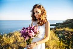 户外婚礼礼服的少妇 一个领域的美丽的新娘在日落 免版税库存图片