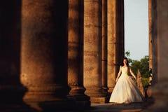 户外婚礼礼服的美丽的新娘在专栏附近 库存照片