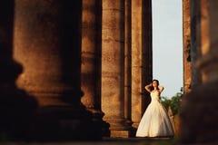 户外婚礼礼服的美丽的新娘在专栏附近 库存图片