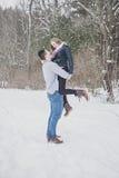 户外嬉戏的年轻夫妇在冬天 免版税图库摄影
