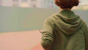 户外实时常平架射击了跟踪从后面的年轻可爱和适合妇女在运行在绿色城市公园的有冠乌鸦 影视素材