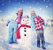 户外小女孩和男孩与雪人 免版税图库摄影