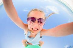 户外小女孩在暑假时获得与父亲的乐趣 颠倒一个孩子的画象在天空背景 库存图片