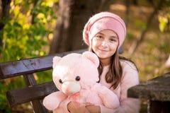 户外小女孩拿着玩具熊的美好的秋天天 免版税库存照片