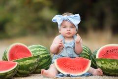 户外小女孩用红色西瓜 免版税库存图片
