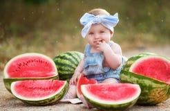 户外小女孩用红色西瓜 免版税库存照片