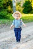 户外小孩孩子 与一个岁男婴佩带的草帽的农村场面 免版税图库摄影