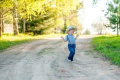 户外小孩孩子 与一个岁男婴佩带的草帽的农村场面 图库摄影