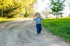 户外小孩孩子 与一个岁男婴佩带的草帽的农村场面 库存照片