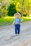 户外小孩孩子 与一个岁男婴佩带的草帽的农村场面 免版税库存照片