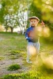 户外小孩孩子 与头戴平顶帽的一个岁男婴的农村场面 库存图片