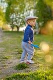 户外小孩孩子 与头戴平顶帽的一个岁男婴的农村场面 免版税库存图片