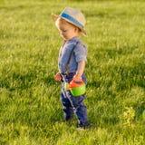 户外小孩孩子 使用喷壶的一个岁男婴佩带的草帽 免版税图库摄影