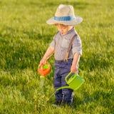 户外小孩孩子 使用喷壶的一个岁男婴佩带的草帽 图库摄影