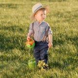 户外小孩孩子 使用喷壶的一个岁男婴佩带的草帽 免版税库存照片