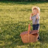 户外小孩孩子 有野餐篮子的一个岁男婴佩带的草帽 免版税库存图片
