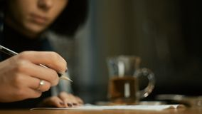 户外少妇坐的咖啡馆秋天在她签署本文写铅笔的毯子包裹了 股票录像