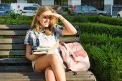 户外少年女小学生13, 14岁画象坐长凳在有书的城市公园 库存照片