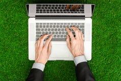 户外工作和商人题目:人的手在一套黑衣服和一个开放笔记本显示姿态在绿色g背景  库存图片