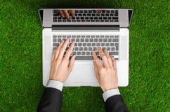 户外工作和商人题目:人的手在一套黑衣服和一个开放笔记本显示姿态在绿色g背景  图库摄影