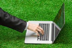 户外工作和商人题目:人的手在一套黑衣服和一个开放笔记本显示姿态在绿色g背景  免版税库存照片