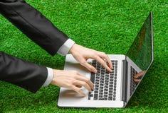 户外工作和商人题目:人的手在一套黑衣服和一个开放笔记本显示姿态在绿色g背景  免版税库存图片