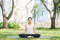 户外年轻亚洲女子瑜伽保留安静并且思考,当实践瑜伽探索内在和平时 免版税库存照片