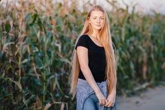 户外年轻可爱的新鲜的看的红头发人妇女生活方式画象有晴朗雀斑华美的特长头发的麦地的 库存照片
