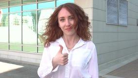 户外年轻美丽的红头发人女学生在走在公园和显示赞许的街道 股票视频