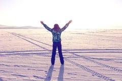户外快乐的妇女用她的在天空的手 在贝加尔湖的冬天 免版税库存图片