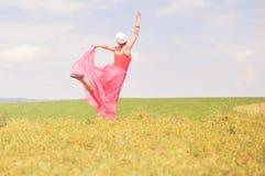 户外快乐的时间:图象的有乐趣典雅的白肤金发的少妇在红色在绿色夏天草甸拷贝空间的礼服愉快的跳舞 库存照片