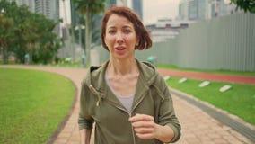 户外慢动作跟踪在运行在绿色城市公园的有冠乌鸦的慢动作年轻可爱和适合妇女的常平架射击 股票录像